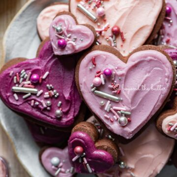 Plate full of chocolate cut out sugar cookies decorated with buttercream frosting and sprinkles | All Images © Beyond the Butter®